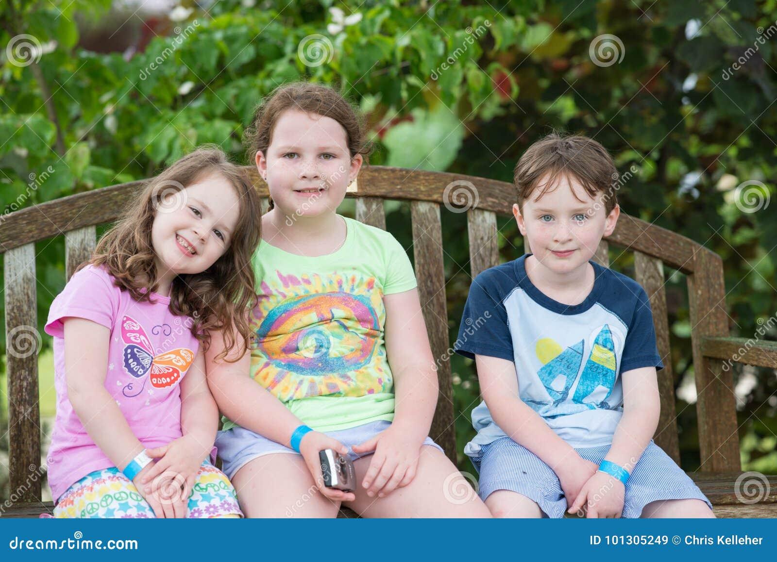 Tre unga syskon som utomhus sitter på bänk