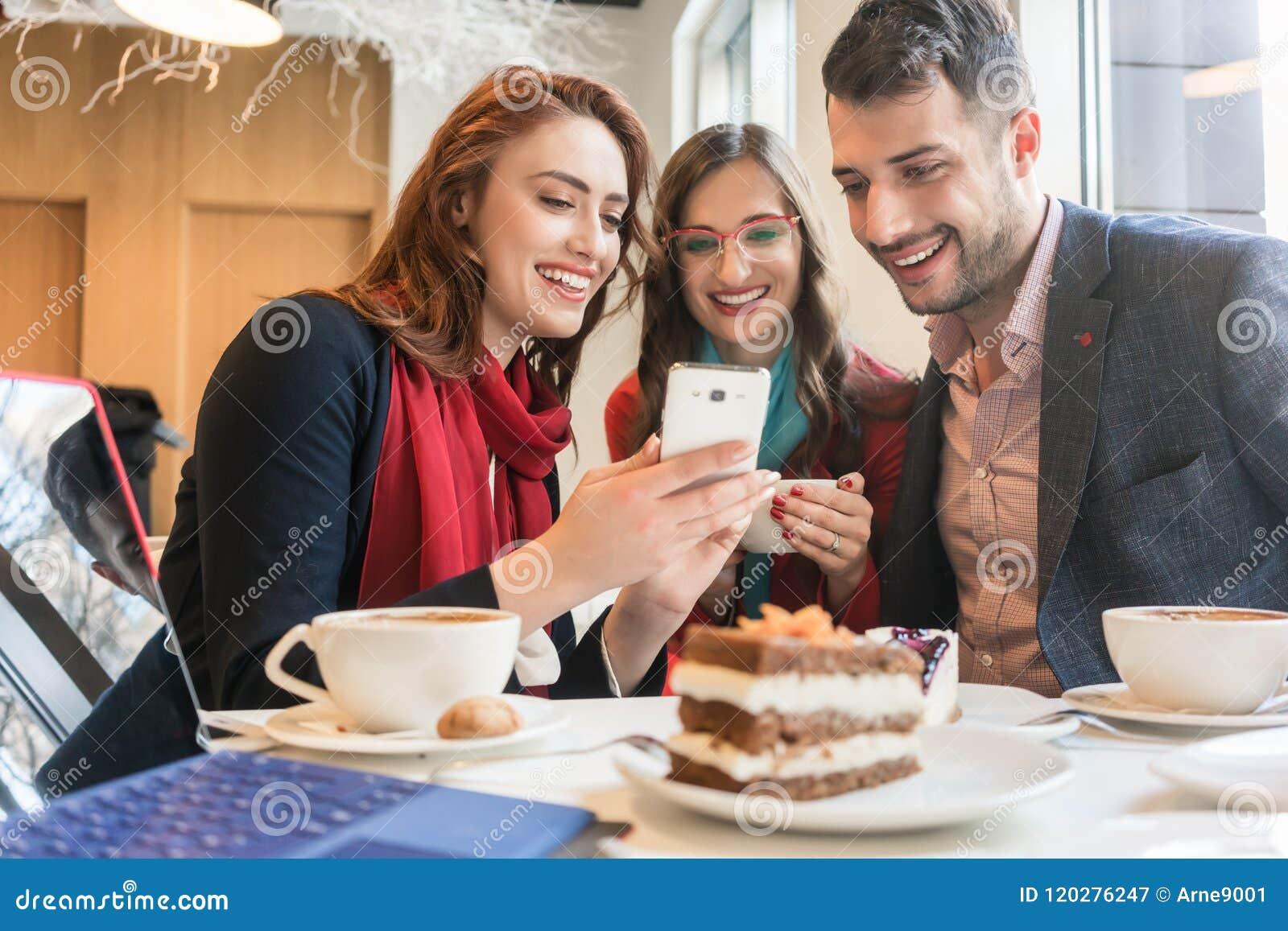Tre unga vänner som använder en mobiltelefon för gyckel under ett kaffeavbrott