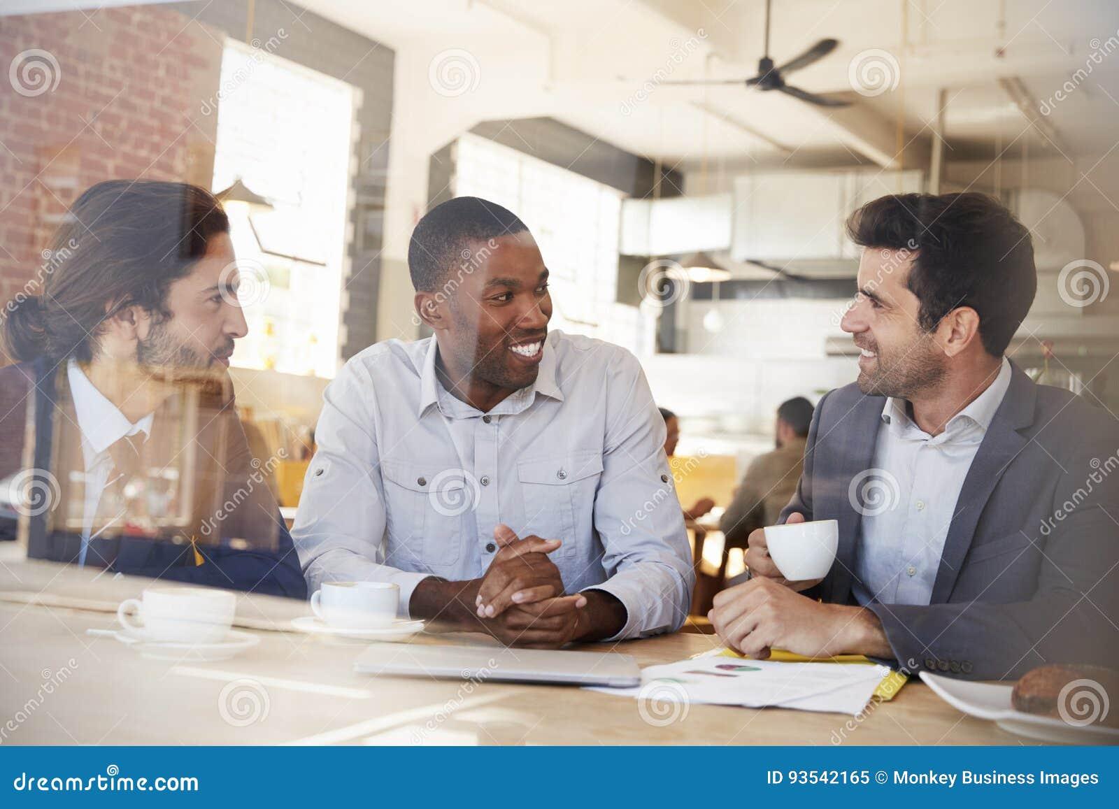 Tre uomini d affari che si incontrano nella caffetteria sparata attraverso la finestra