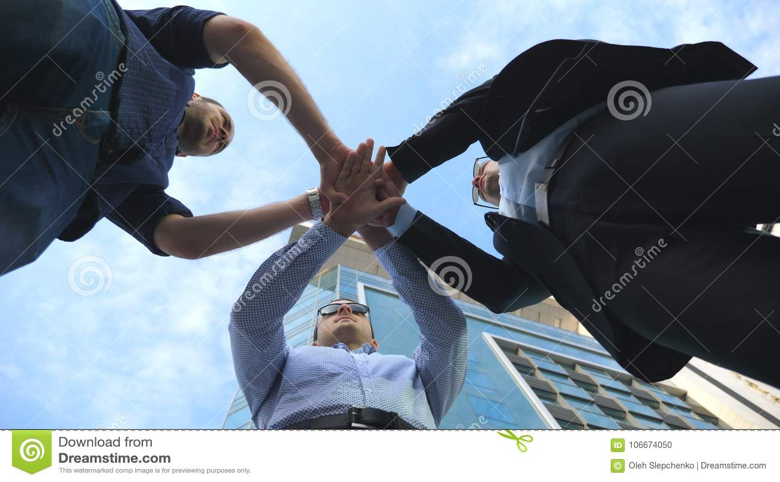 Tre uomini di affari che stanno insieme ufficio vicino all aperto e braccio impilato nell unità e nel lavoro di squadra mani dell