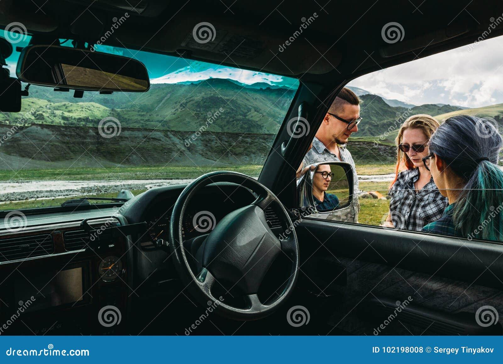 Tre vänner nära bilen diskuterar rutten i resan