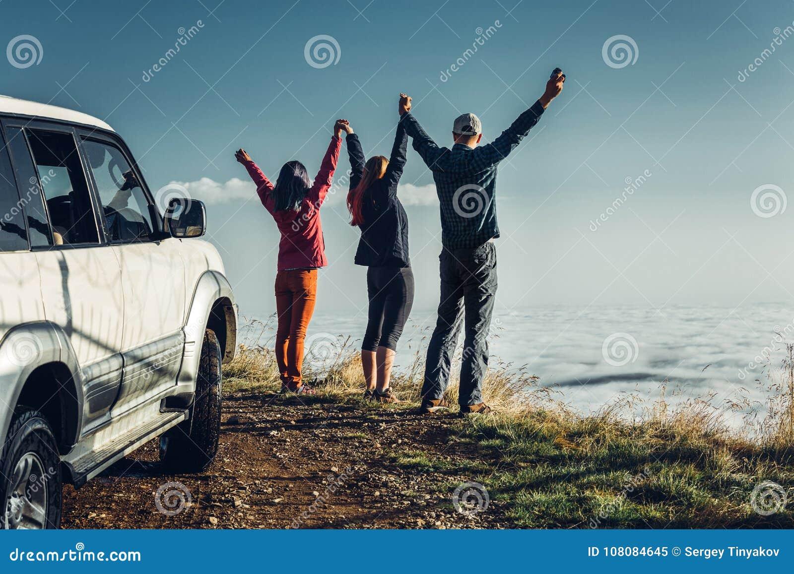 Tre vänner sammanfogade händer och lyftte upp deras händer och att tycka om sikten av utomhus- Semesterresabegrepp
