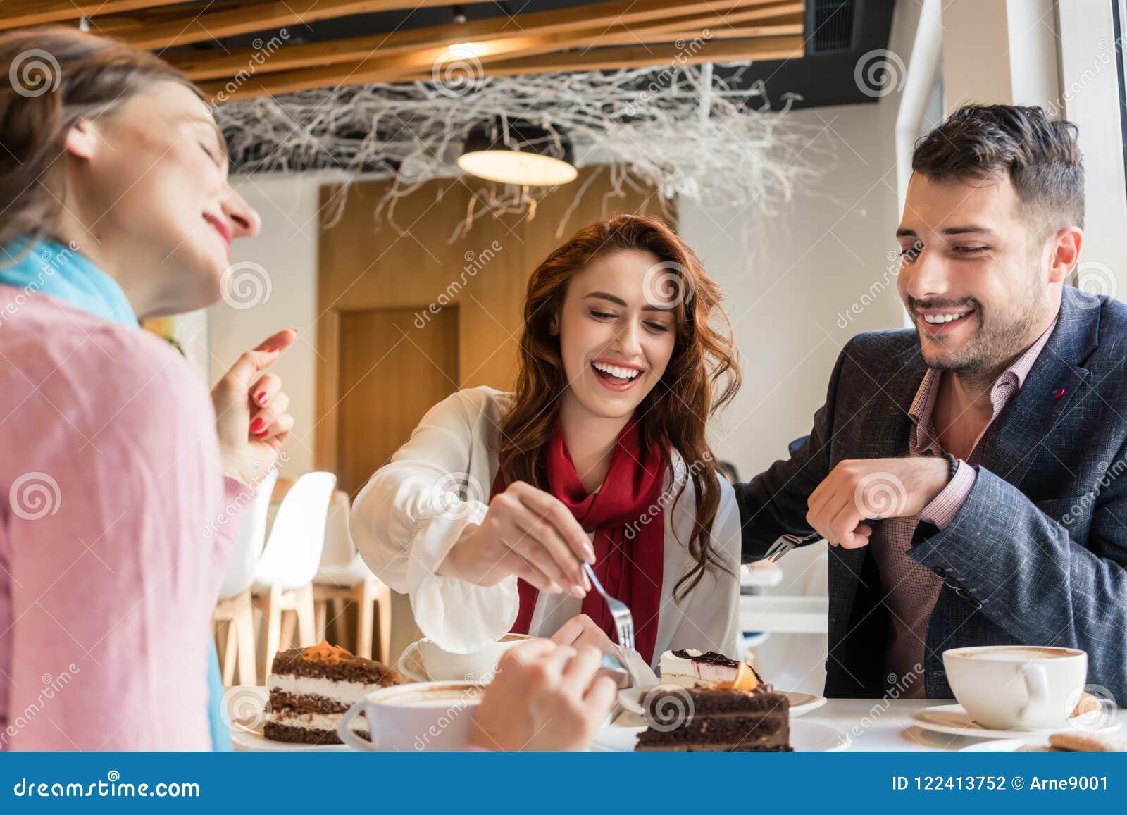 Tre vänner som ler, medan äta läckra kakor i deras fuskdag