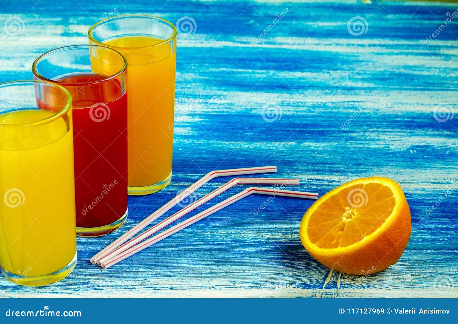 Tre vetri delle bibite sono su un fondo blu Fette di arancio Bevande di estate e stile di vita sano