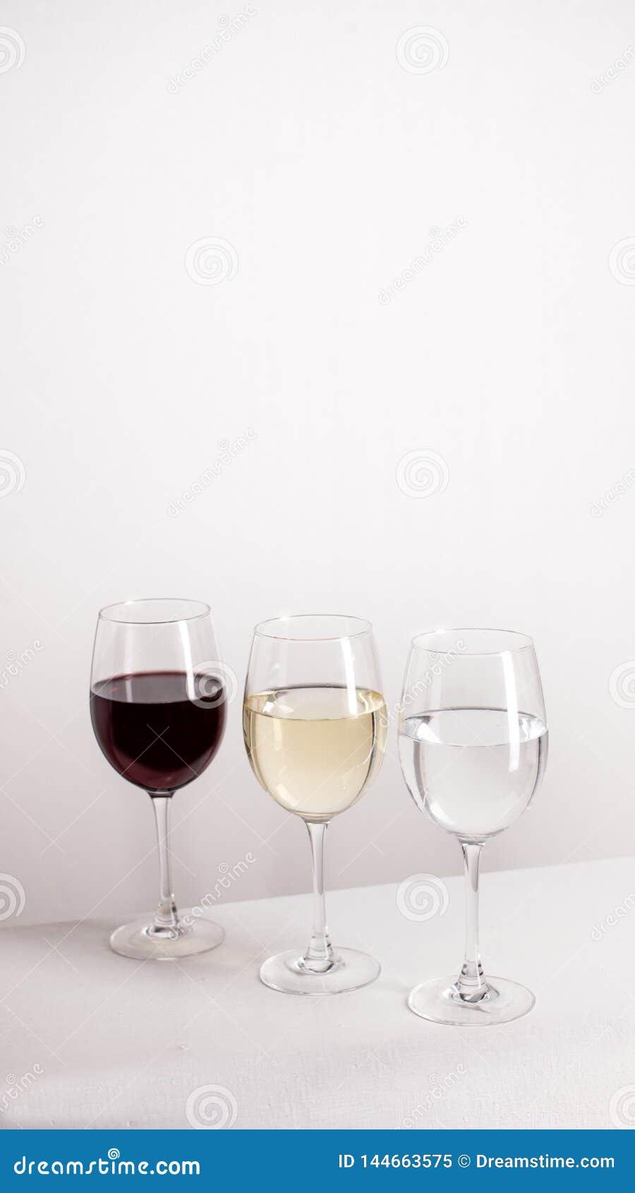 Tre vetri di vino rosso e bianco e di acqua che stanno in una linea su fondo grigio