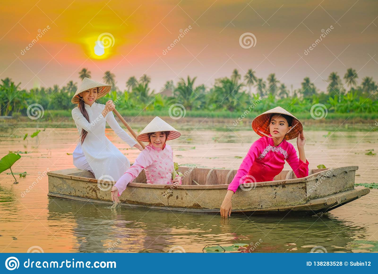 Tre vietnamesiska flickor ror i lotusblommaträdgården