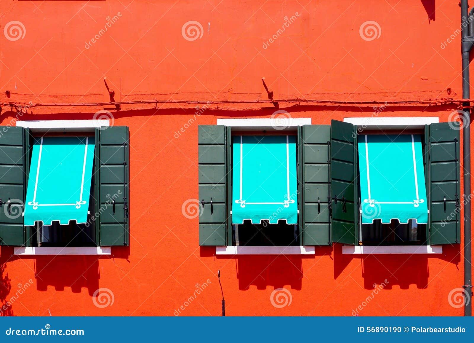 Tre Windows con il baldacchino blu in Burano sulla parete arancio rossa