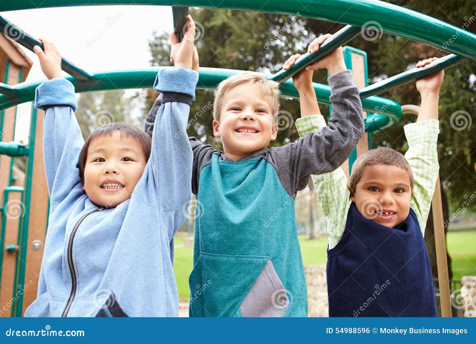 Tre Young Boys på klättringram i lekplats