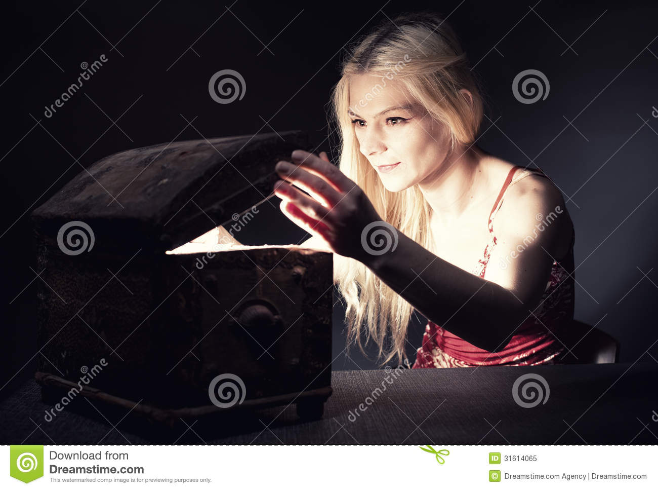 Young blond woman securing her treasure in a retro wooden chest.
