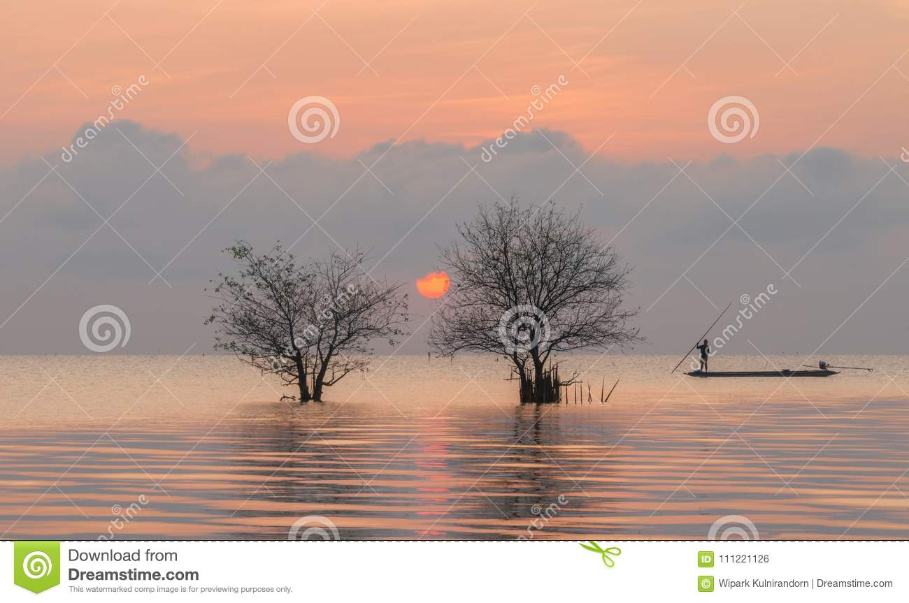 Trees and fisherman in the lake with beautiful sunrise and sky.