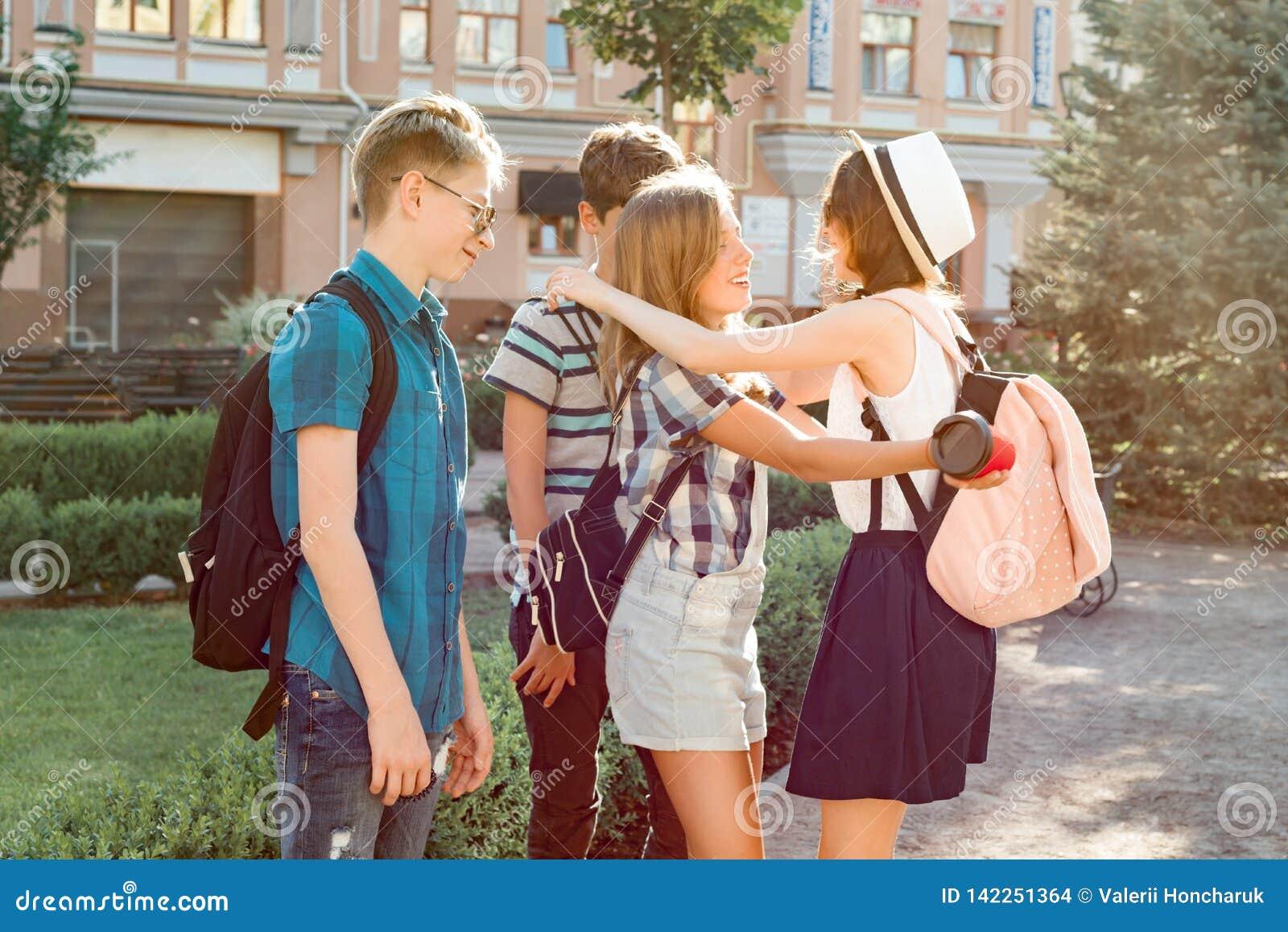 Treffen von lächelnden Freundjugendlichen in der Stadt, glückliche junge Leute, die, umarmend sich grüßen, hoch fünf gebend Freun