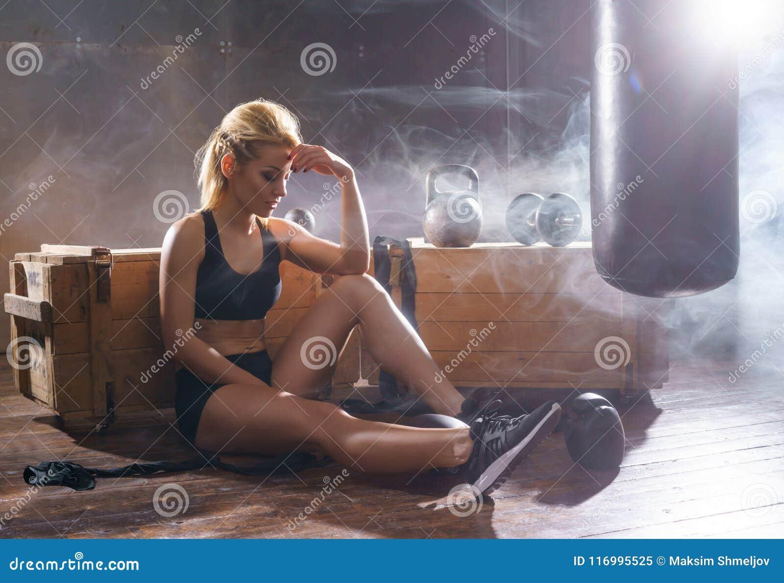 Treinamento apto e desportivo da jovem mulher no gym do undergorund Saúde, esporte, kickboxing, conceito das artes marciais
