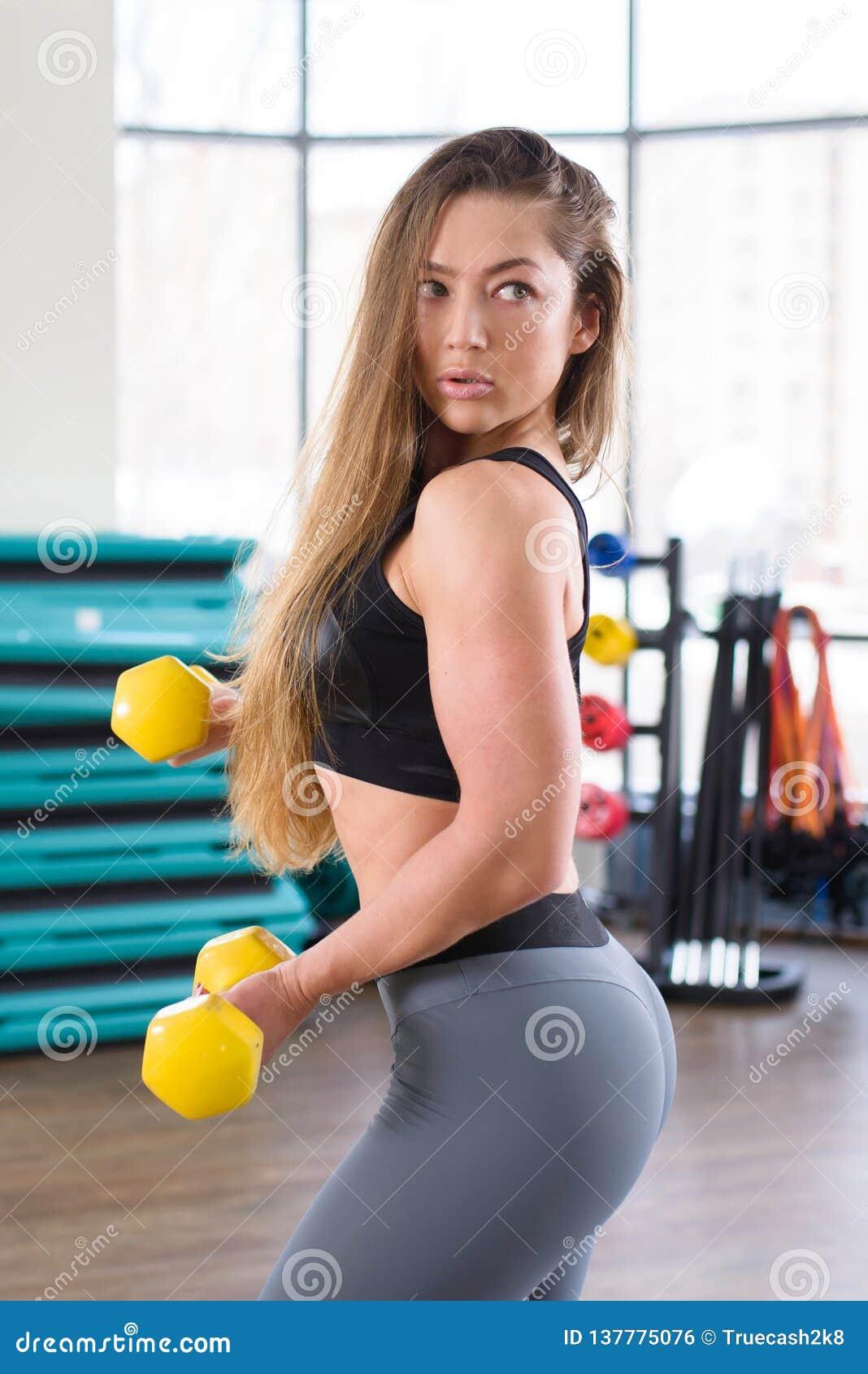 Treinamento atlético novo da mulher com pesos no gym Aptidão e conceito saudável do estilo de vida Menina caucasiano bonita