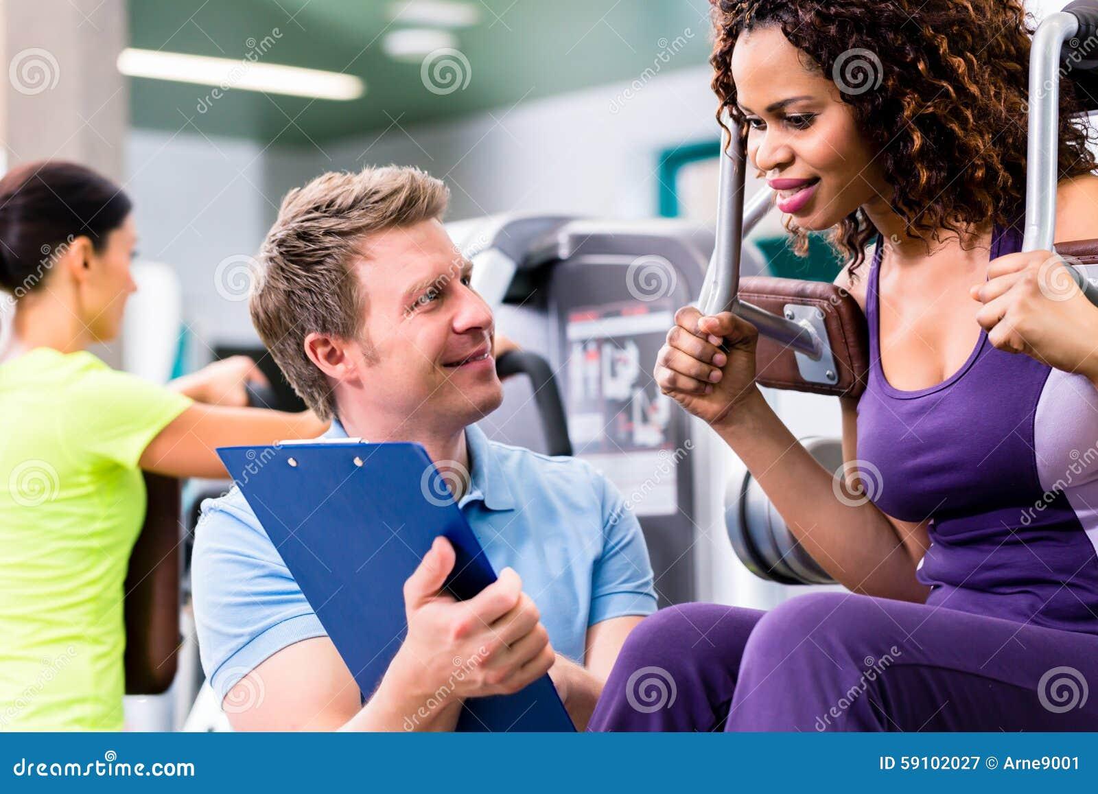 Treinamento da aptidão no gym - mulher negra e instrutor pessoal