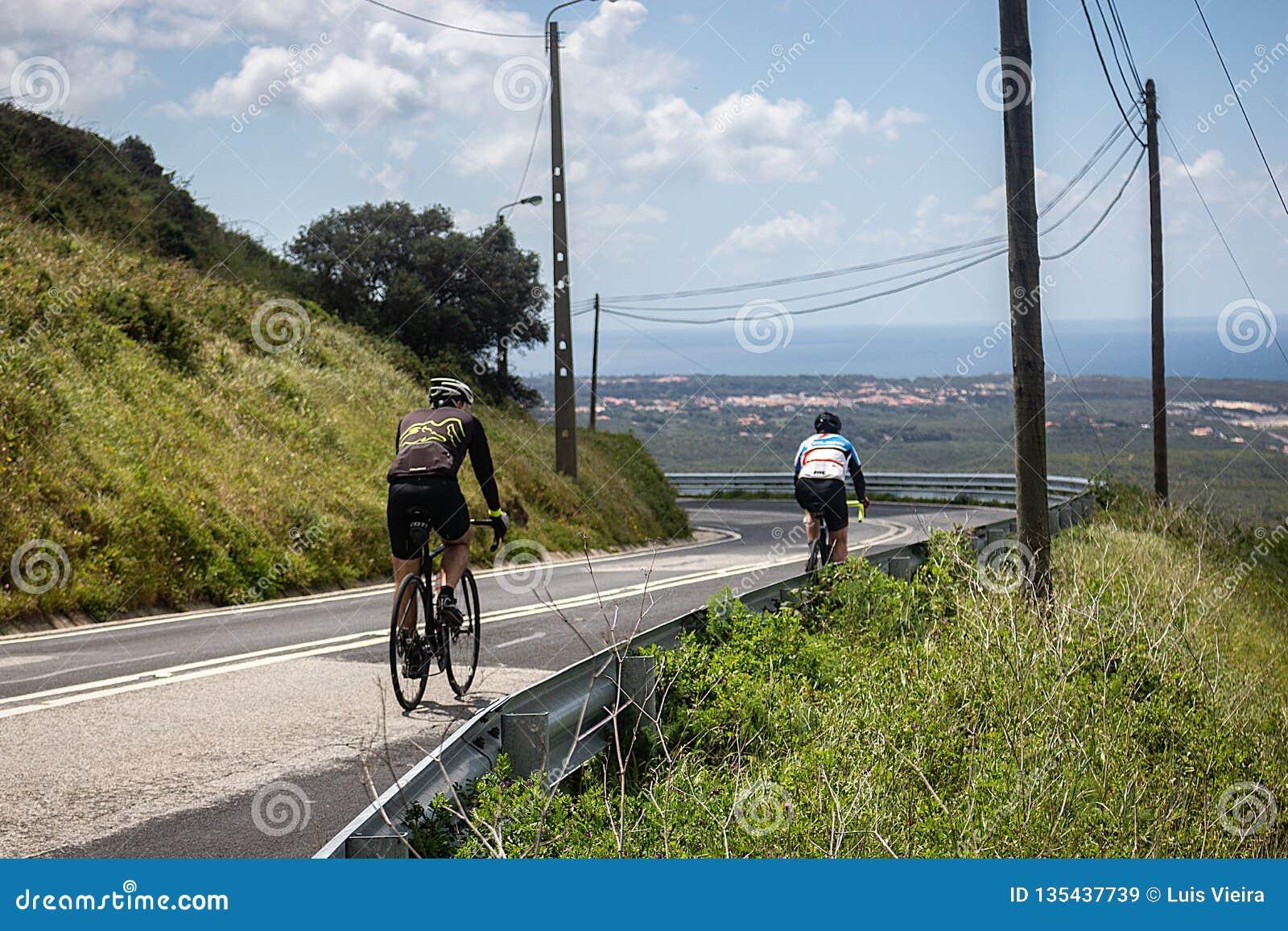 Treinamento de dois ciclistas nas estradas dos cascais