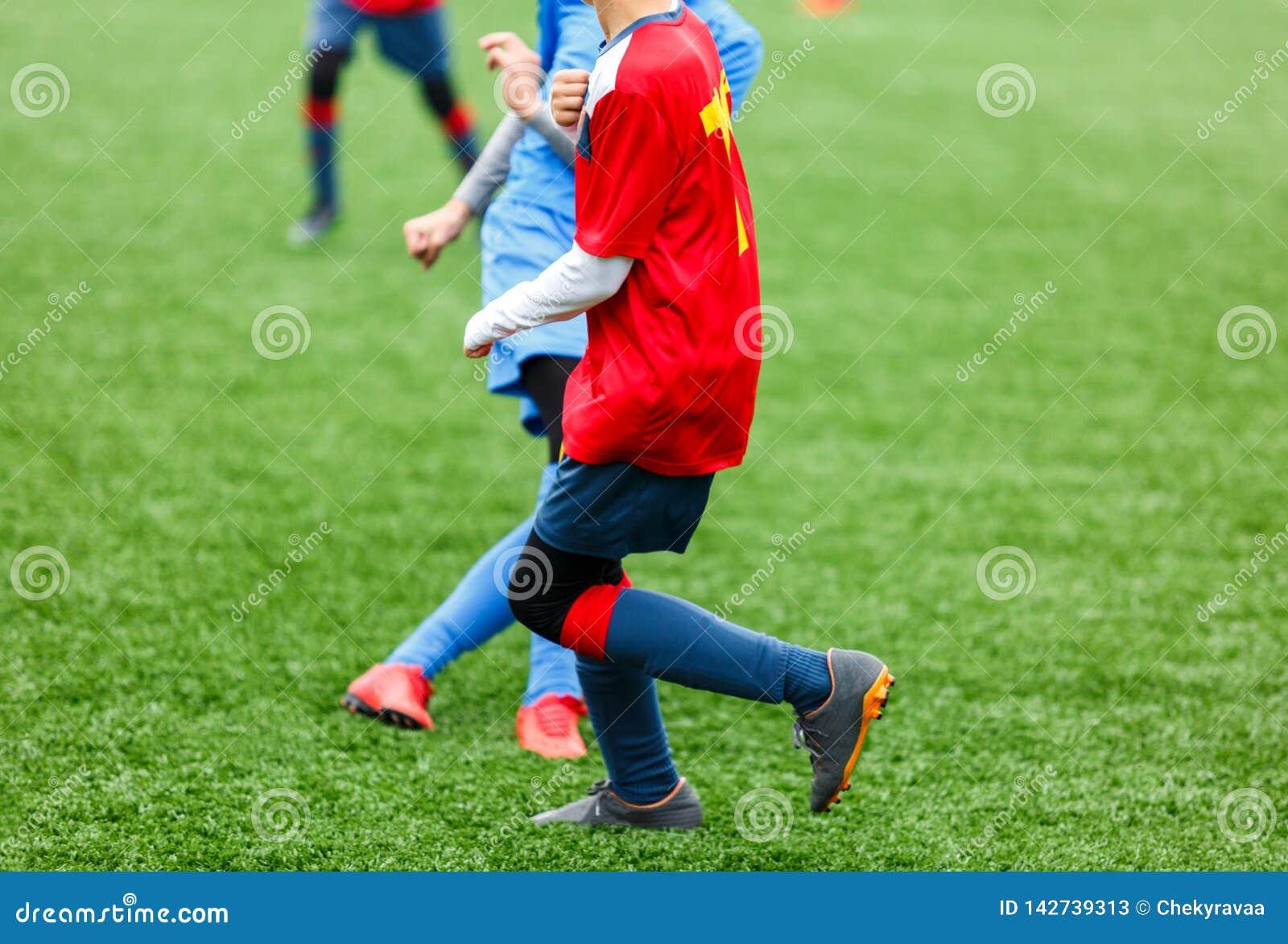 Treinamento do futebol para crianças Meninos no sportswear vermelho azul no campo de futebol Os jogadores de futebol novos pingam