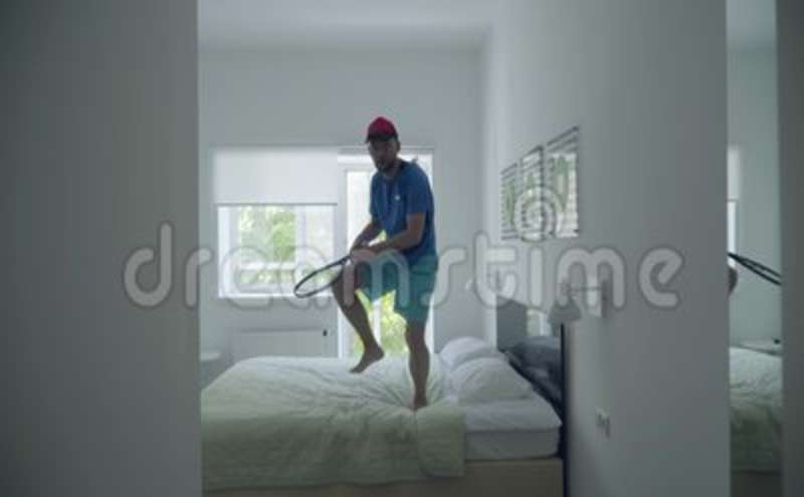 Treinamento do homem novo para jogar o tênis que está na cama na sala de hotel confortável Estilo de vida ativo Esportes e recrea video estoque