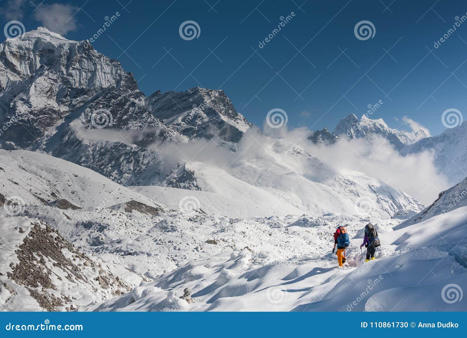 Trekkers пересекая ледник Gokyo в долине Khumbu на пути к Eve