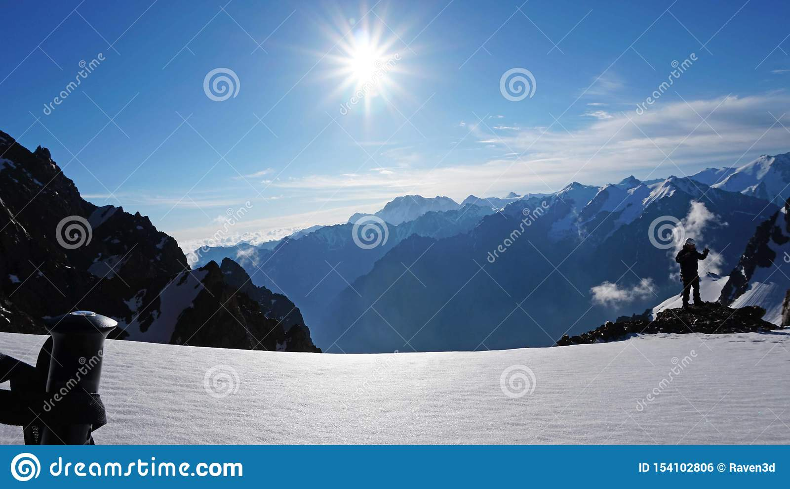 Trekking поляки на предпосылке солнца, снежных гор, голубого неба и облаков