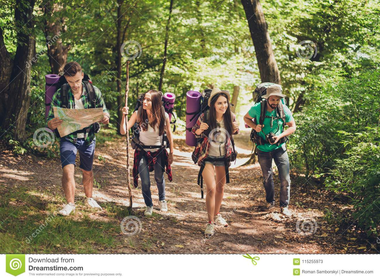 Trekking, camping and wild life concept. Four best friends are hiking in the spring woods, the guy is checking the route on a map,