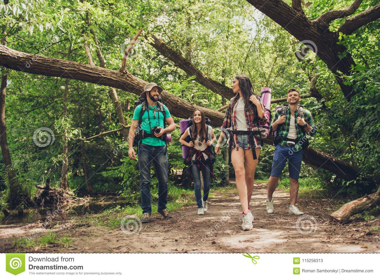 Trekking, camping and wild life concept. Two couples of friends are walking in the sunny spring woods, talking and laughing, all a