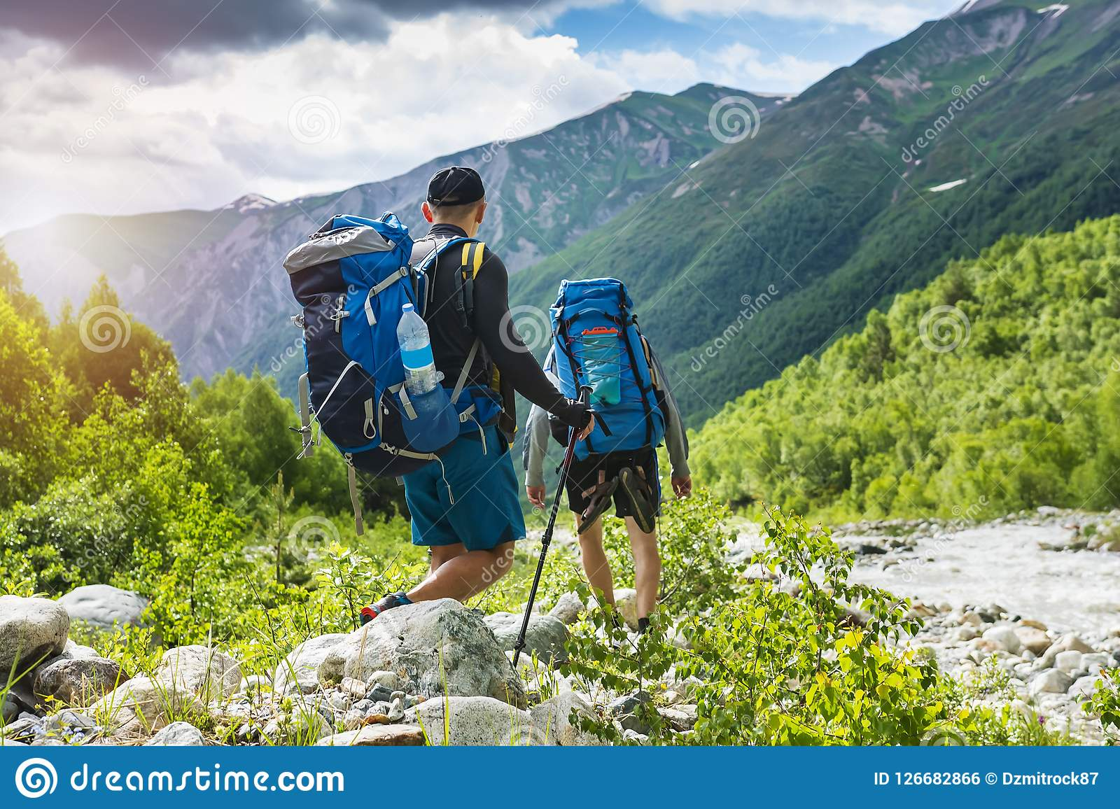 Trekking in mountains. Mountain hiking. Tourists with backpacks hike on rocky way near river. Wild nature with beautiful views.
