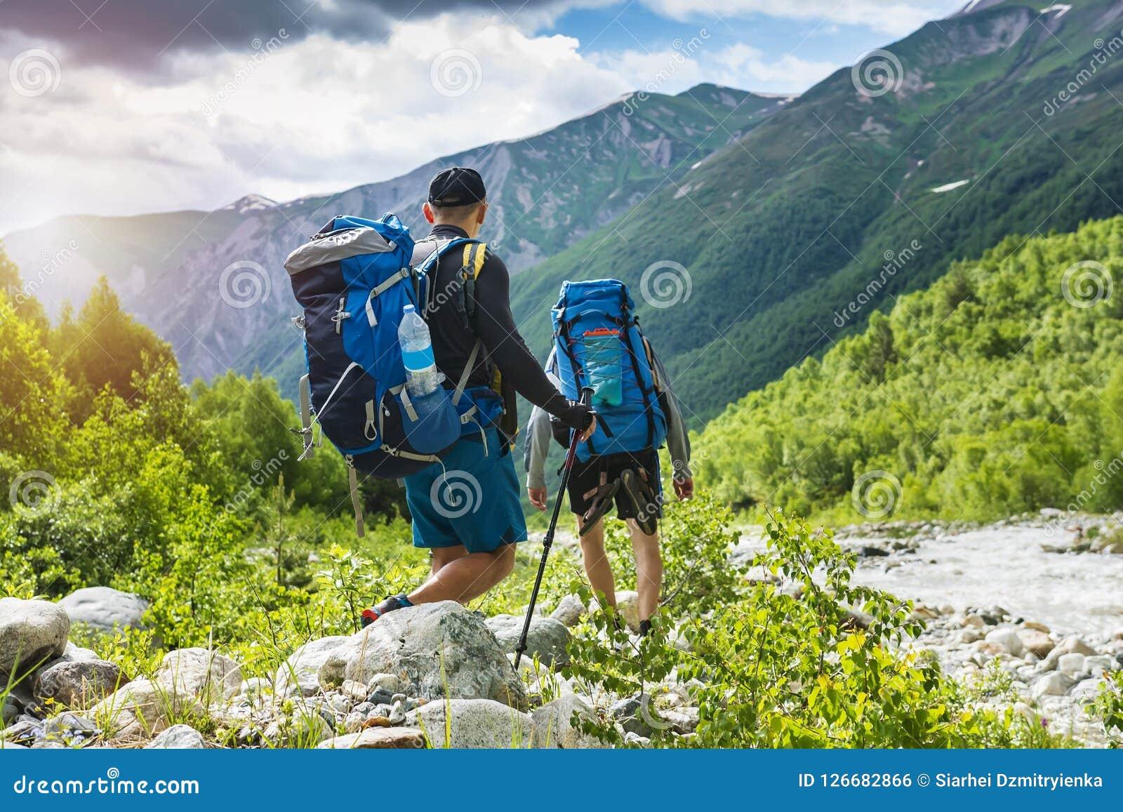 Trekking nas montanhas Caminhada da montanha Os turistas com trouxas caminham na maneira rochosa perto do rio Natureza selvagem c