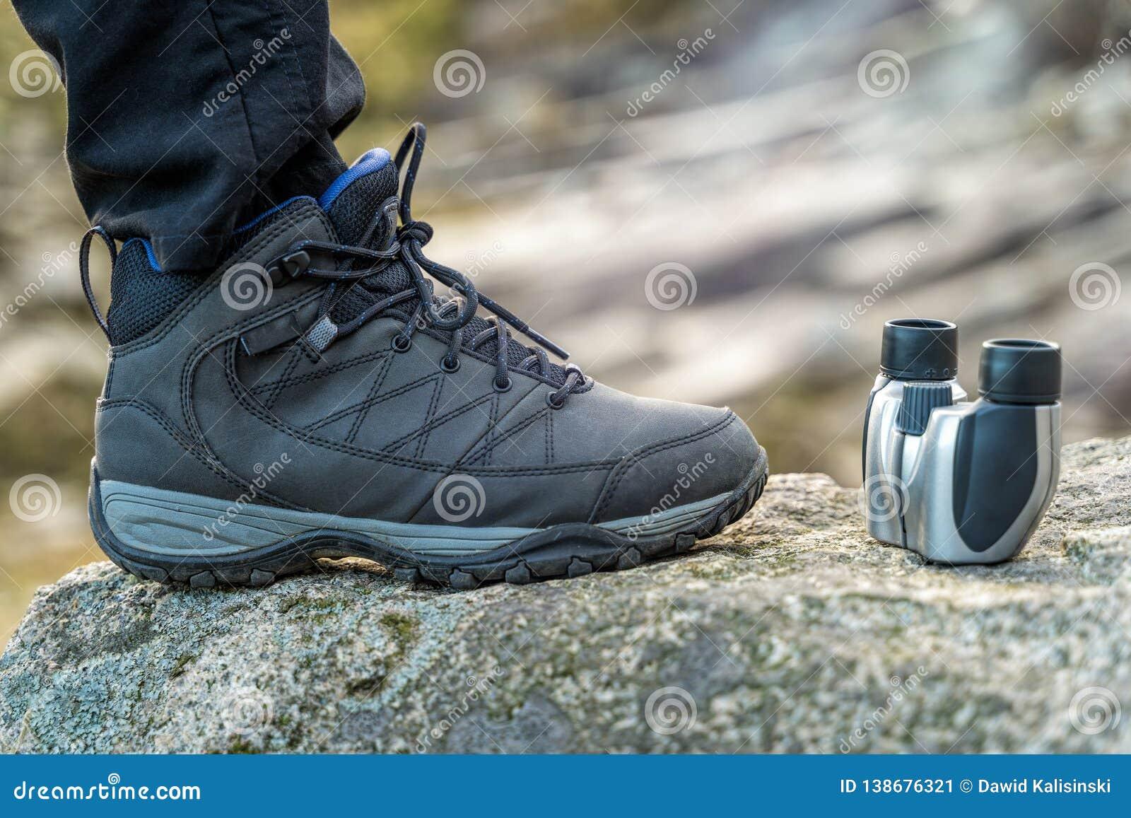 Trekking Shoe And Binocular Closeup On A Rock In The