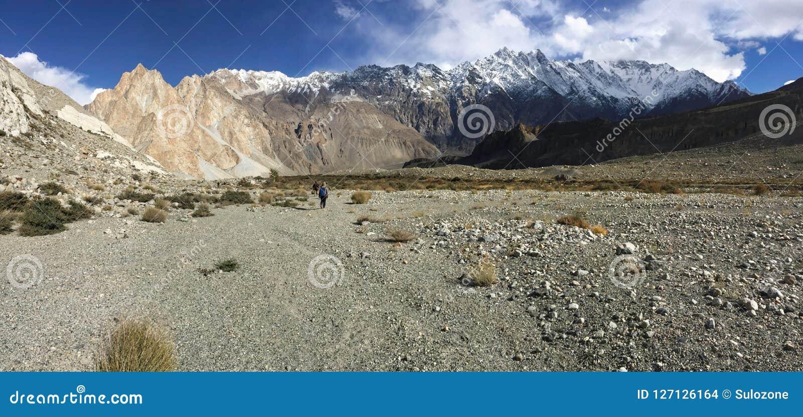 Trekking trail in Passu show drought landform, snow capped mountains in Karakoram range.