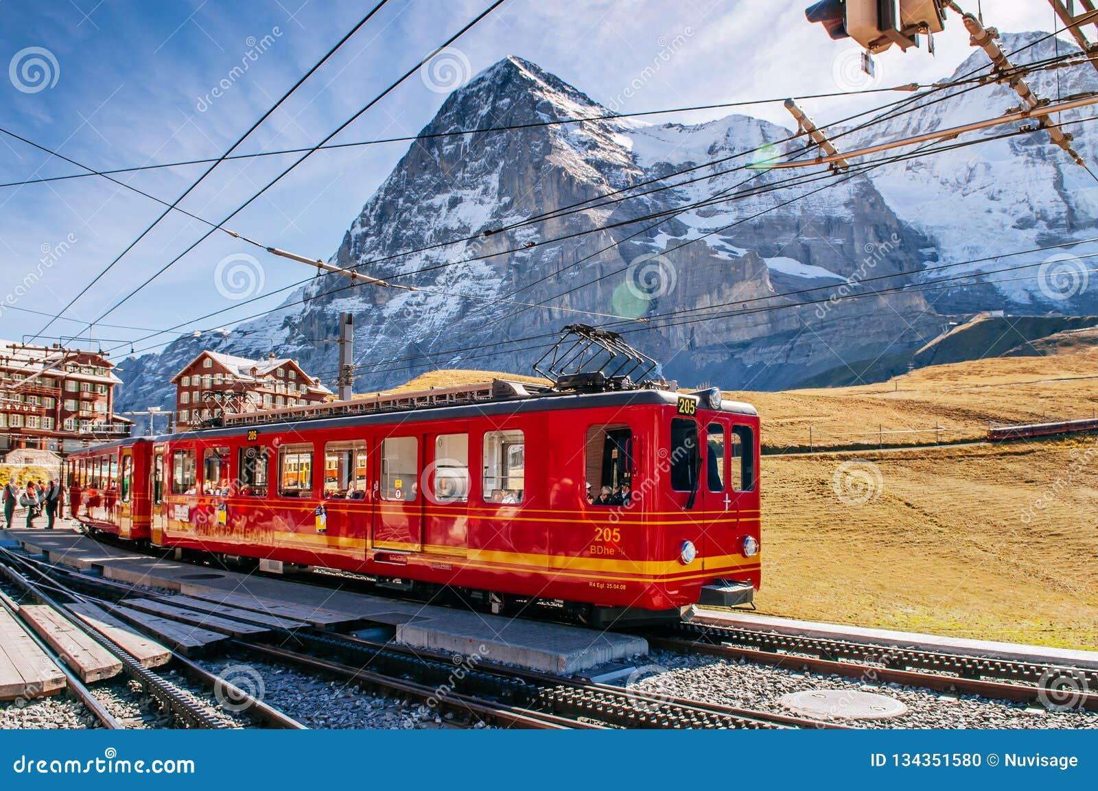 Trem da estrada de ferro de Jungfrau na estação de Kleine Scheidegg com pico de Eiger e de Monch