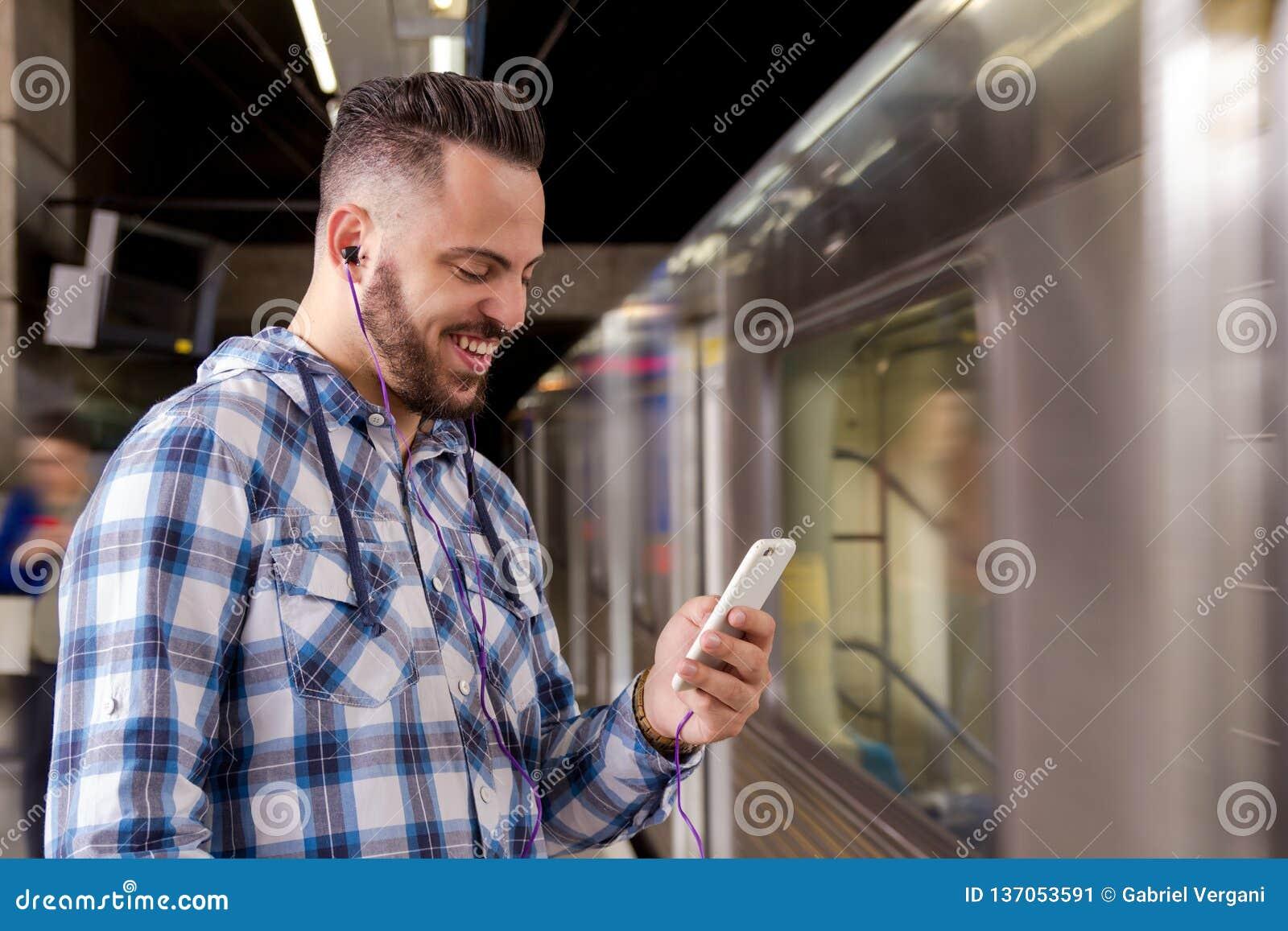 Trem de espera do viajante do estudante que escuta a música em um smartphone Conceito do lazer, uma comunicação, meio social