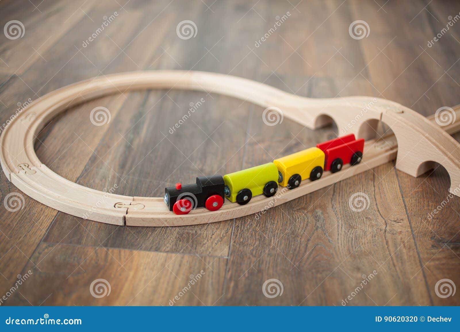 Trem de madeira do brinquedo na estrada de ferro com ponte de madeira Limpe o assoalho laminado
