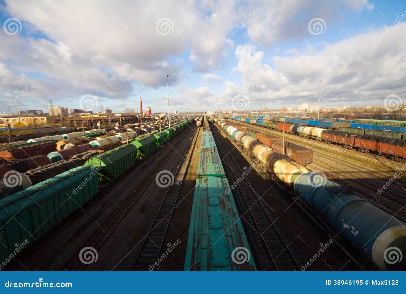 Trem de mercadorias com os recipientes de carga da cor