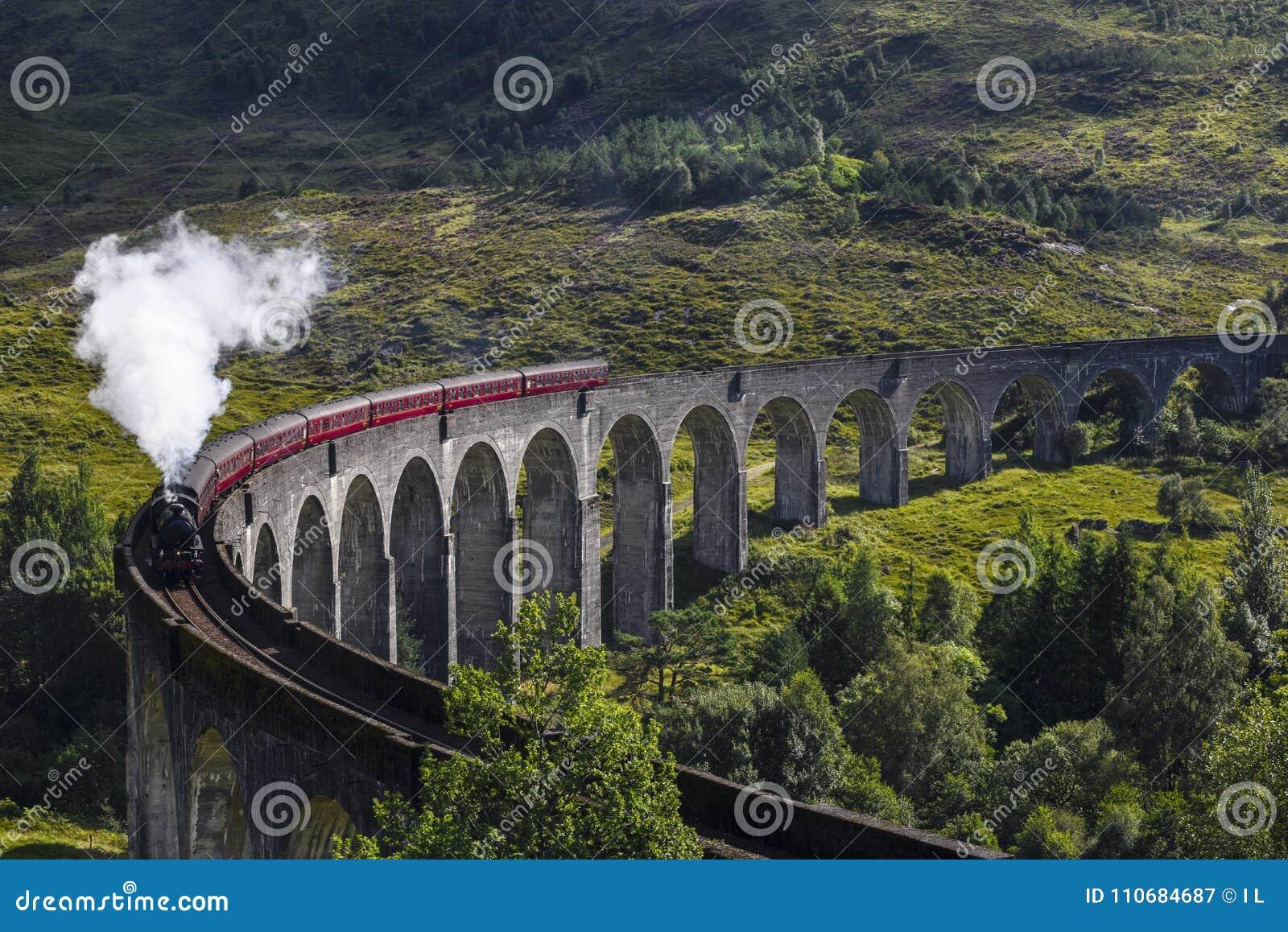 Trem do vapor de Jacobite no viaduto de Glenfinnan no Loch Shiel, Mallaig, montanhas, Escócia