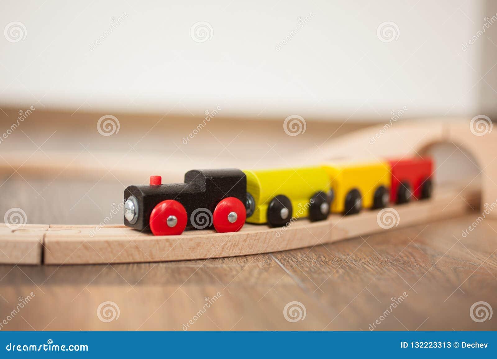 Tren de madera del juguete en el ferrocarril con el puente de madera Limpie el piso laminado