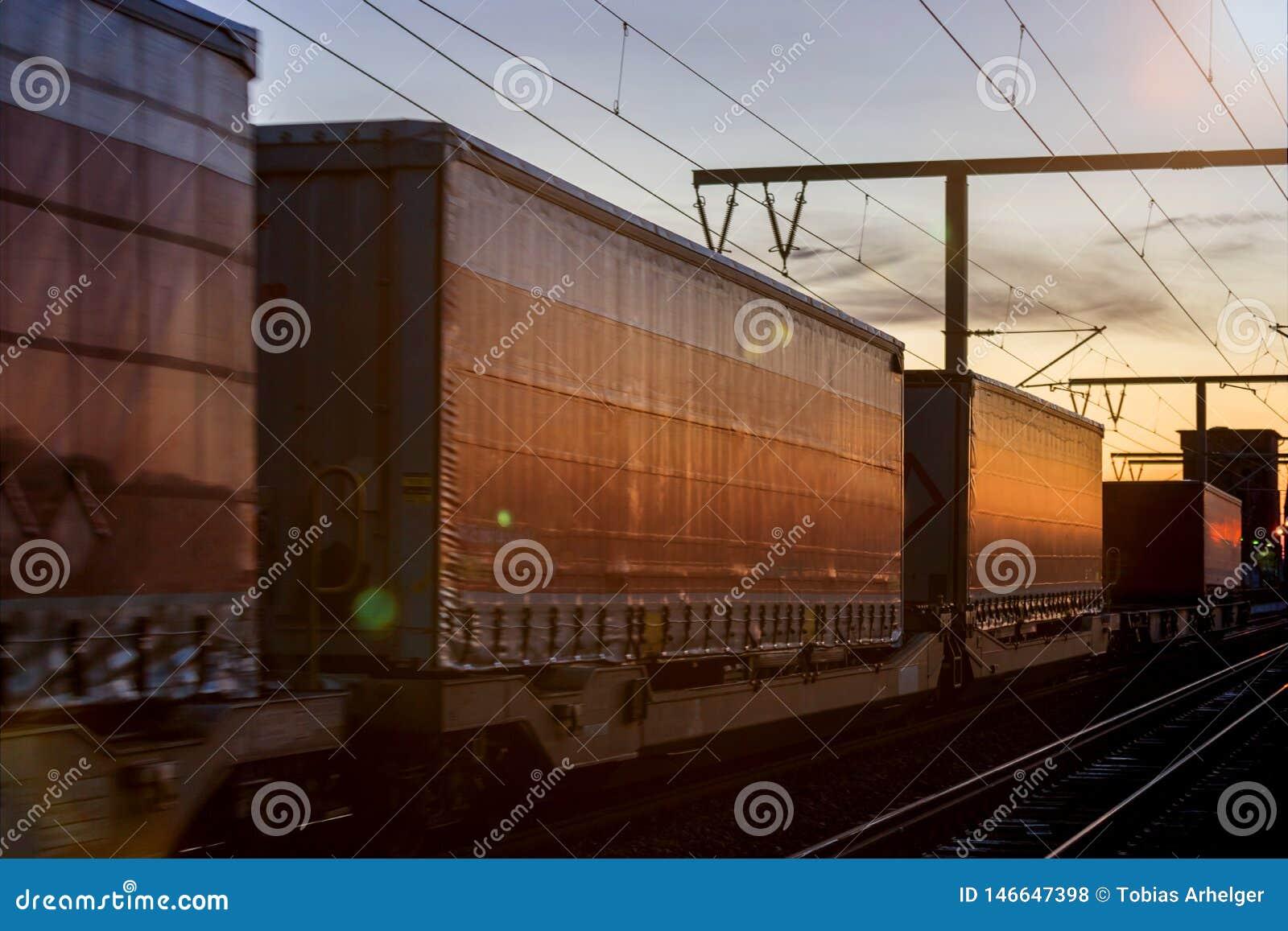 Tren del cargo del envase en el sol de igualación