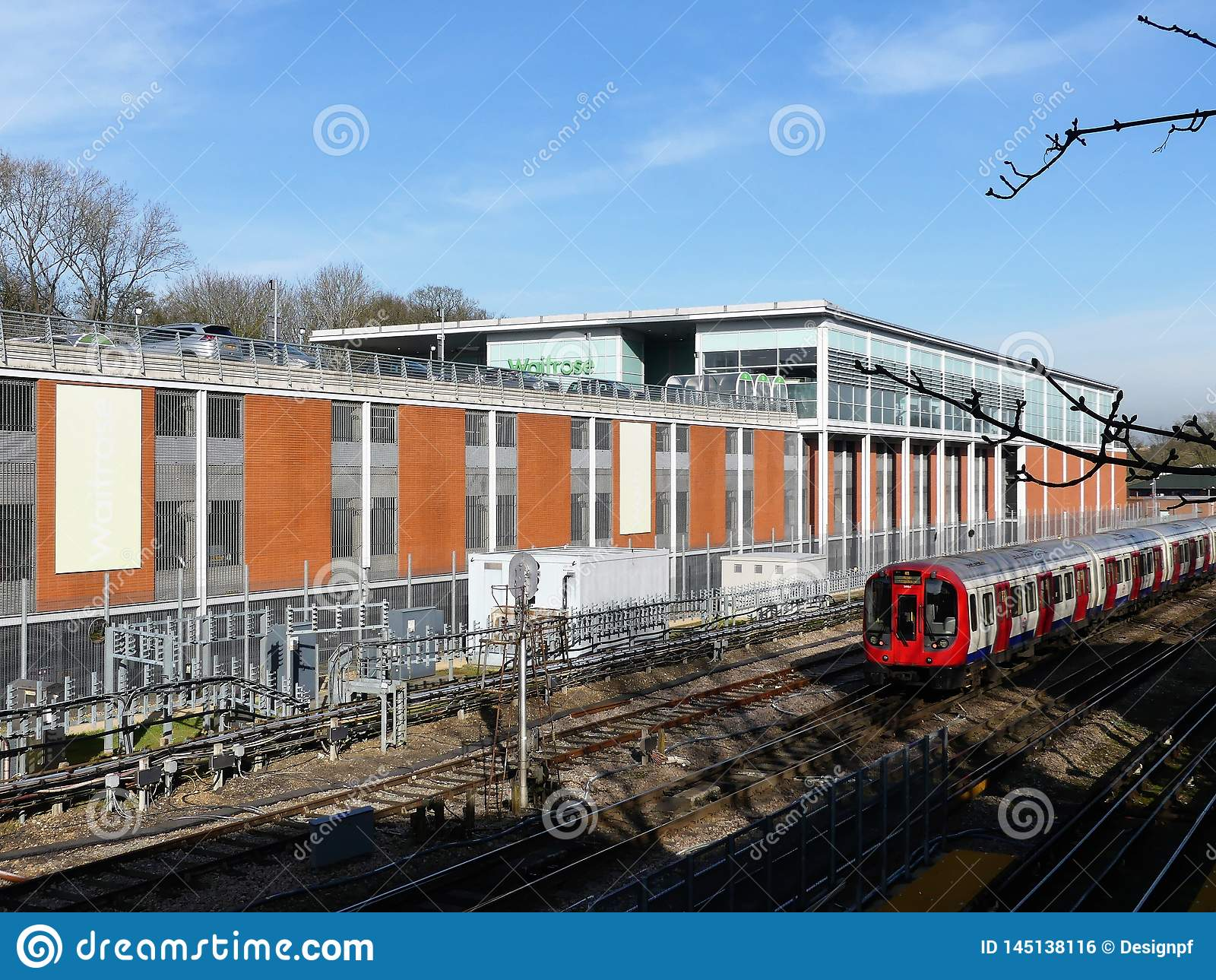 Tren subterráneo de Londres que pasa la tienda del supermercado de Waitrose en Rickmansworth