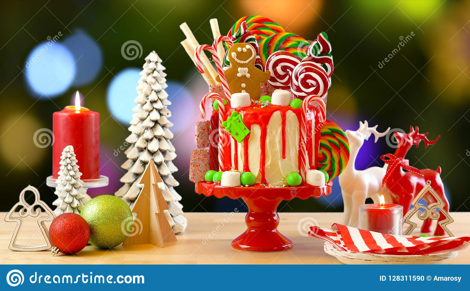 on trend festive candyland christmas drip cake against festive christmas tree bokeh lights background