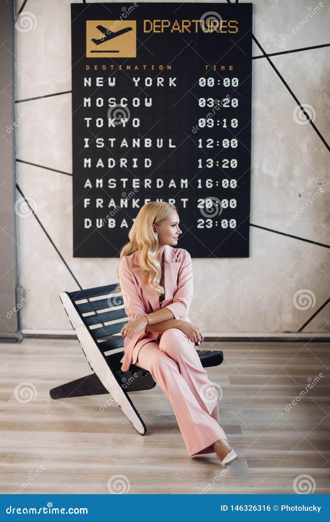 Trendig dam i den rosa dräkten som väntar på hennes flyg i flygplats
