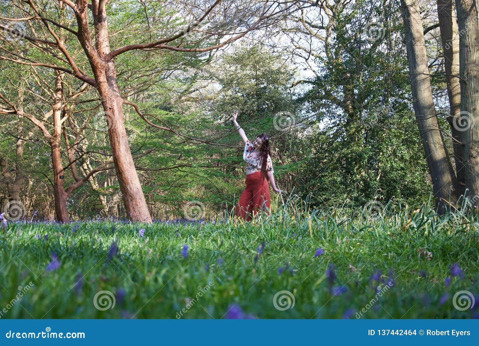 Trendig dam som poserar i ett engelskt trä med blåklockor och träd