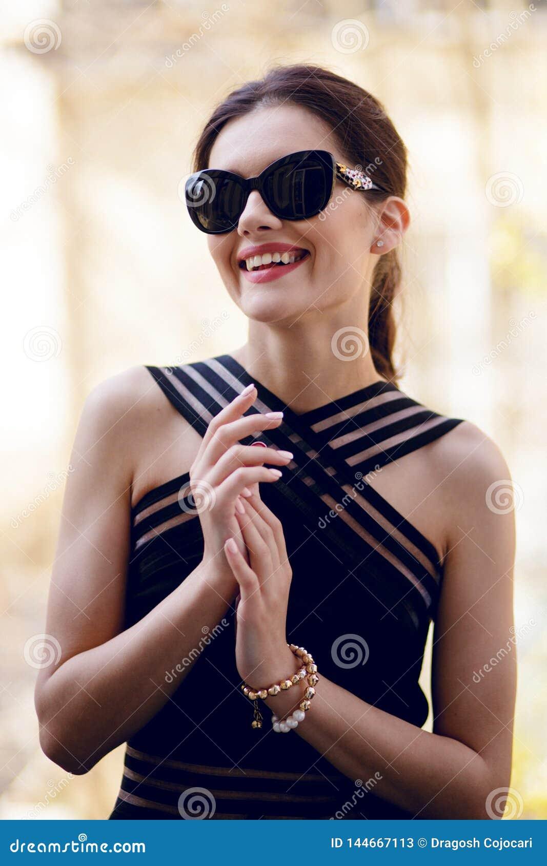 Trendig kvinna med sublimt från och att bära i en elegant svart klänning och sunglass, i dagen som poserar på balkong
