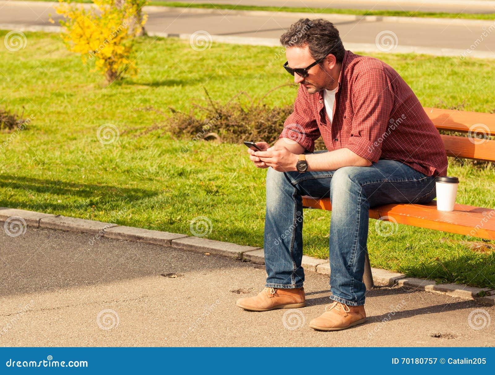Trendig man som kopplar av på en bänk i parkera
