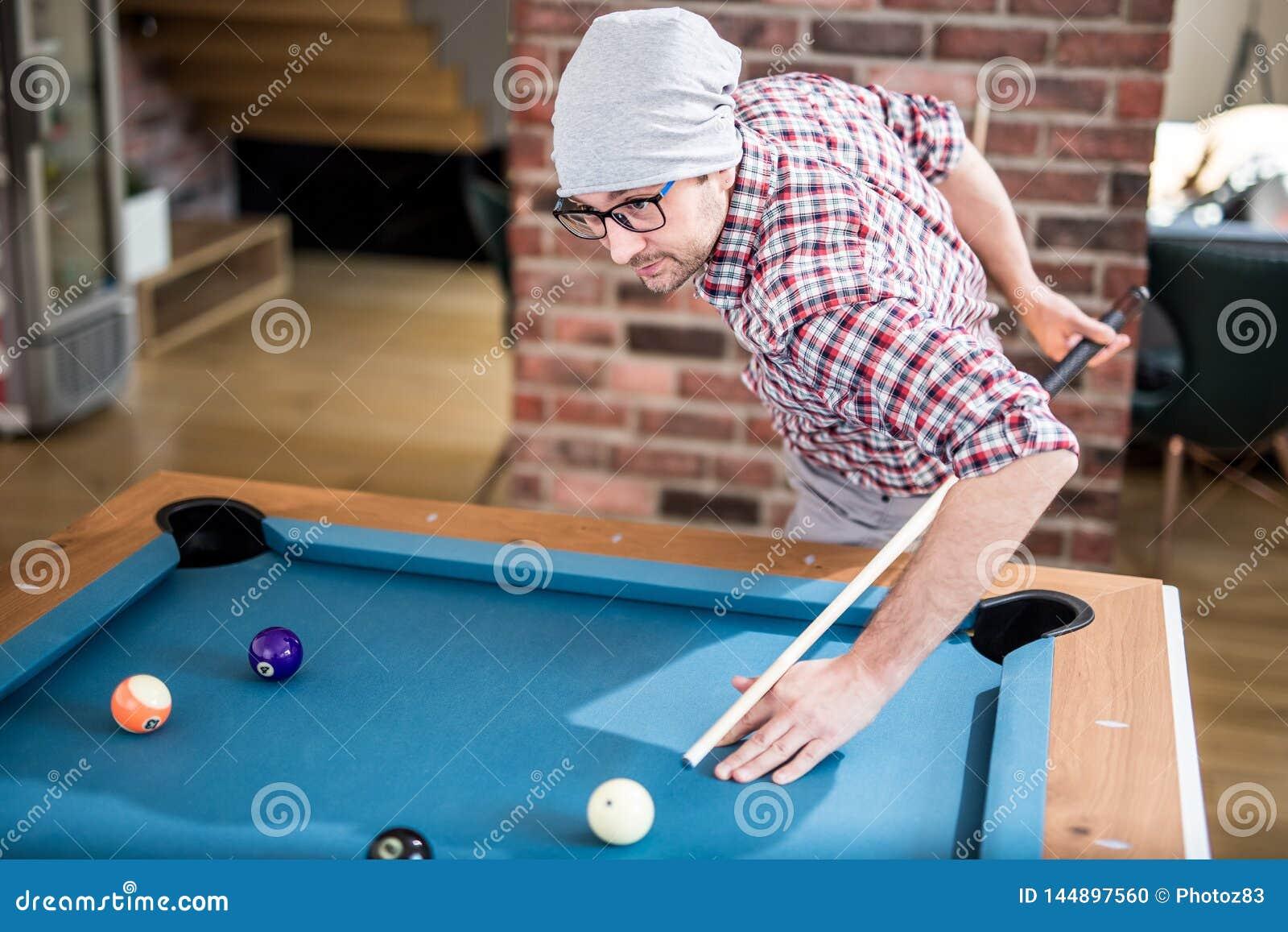 Trendig stads- man som siktar billiardbollen, genom att rymma pinnen bak hans baksida