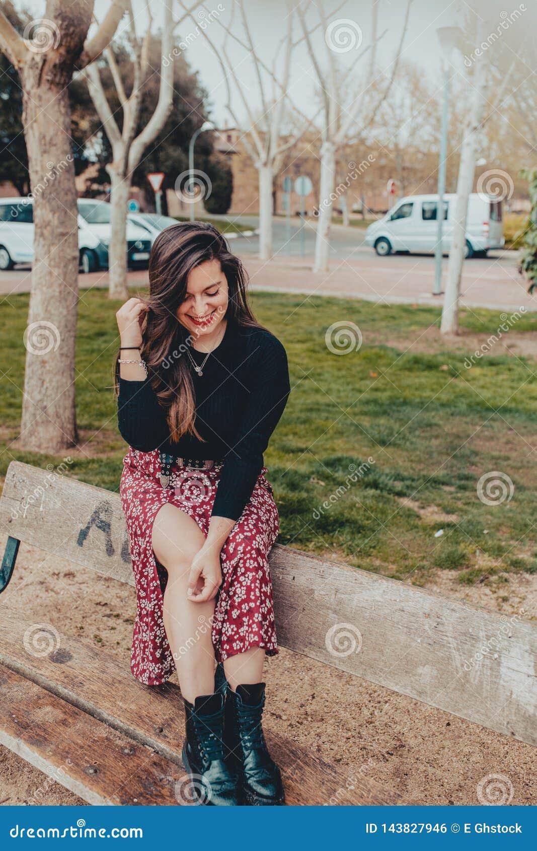 Trendig ung flicka som sitter på en bänk som shyly skrattar