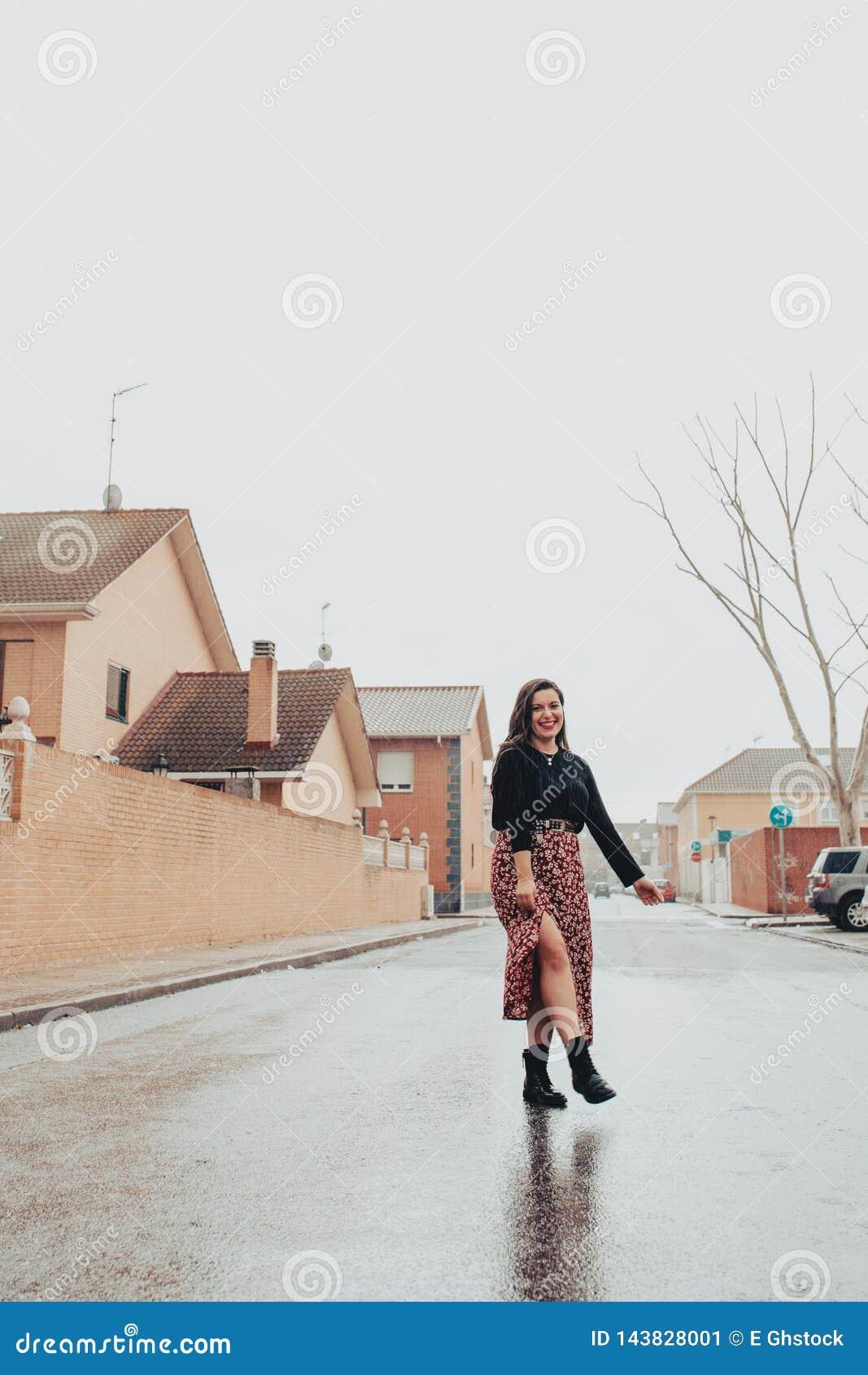 Trendig ung kvinna som hoppar i regnet