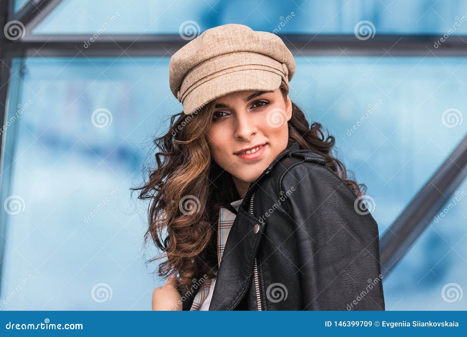 Trendig ung kvinna som utomhus poserar mot exponeringsglasfönster