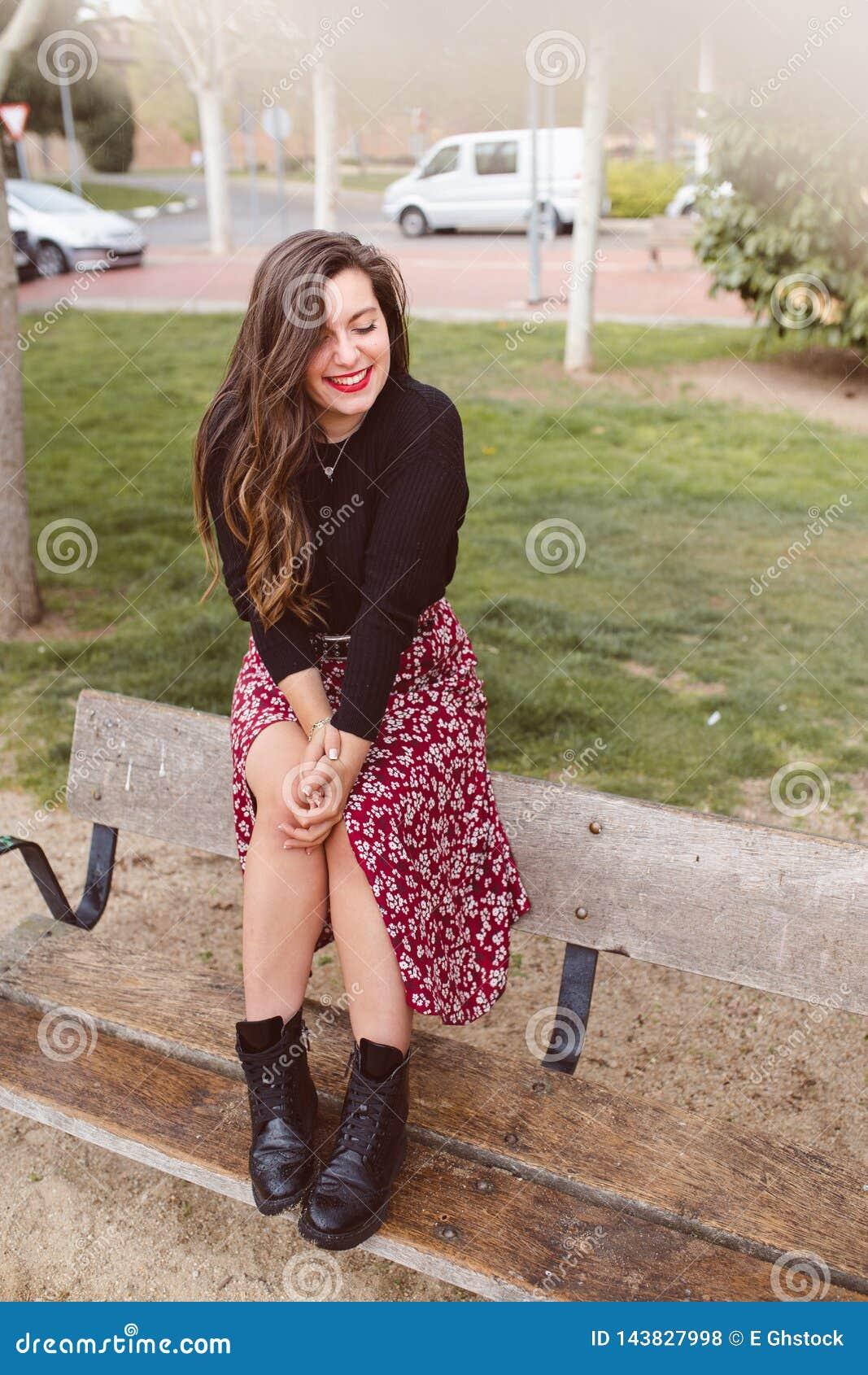 Trendig ung och gladlynt kvinna som sitter p? en b?nk som shyly skrattar