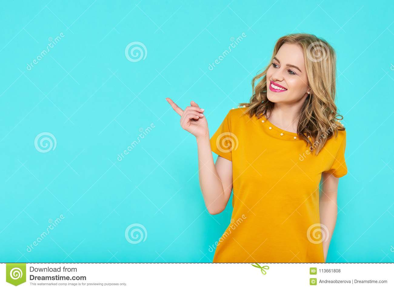Trendy attractive young woman wearing mustard color summer dress posing over pastel blue background. Front view of smiling woman.