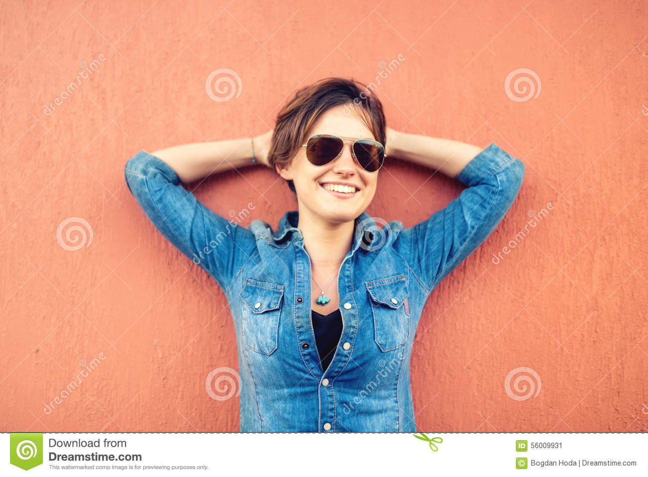 Trendy brunette girl, making face expressions, smiling and laughing against orange background, isolated. Modern lifestyle