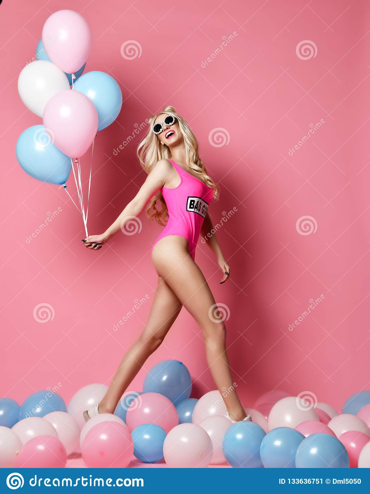 Trendy cheerful blonde woman on birthday party having fun walking with pastel color air balloons